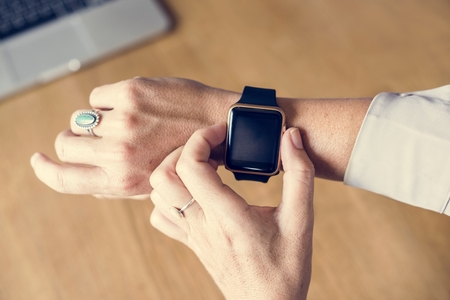 Hand setting a smartwatch on another hand