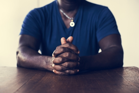 Closeup of black man sitting with interlocked fingers Stock fotó