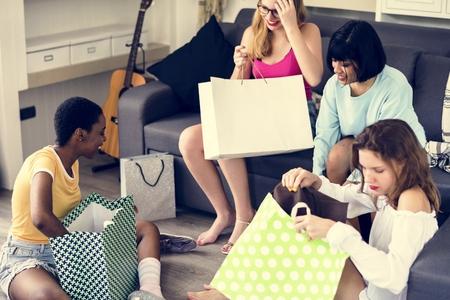 Women showing friends shopping items