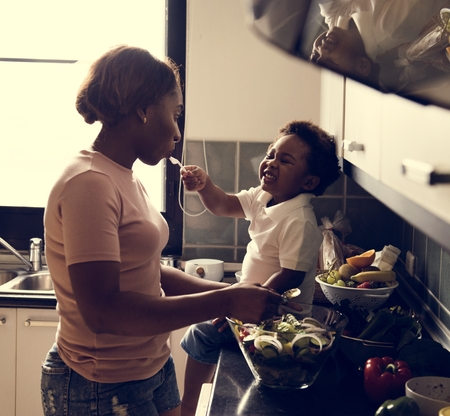 Black kid feeding mother with cooking food in the kitchen Imagens