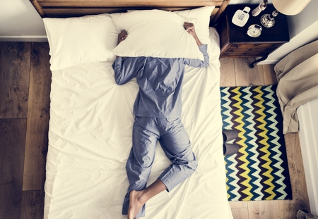 Man on bed insomnia and noise pollution concept Stock Photo