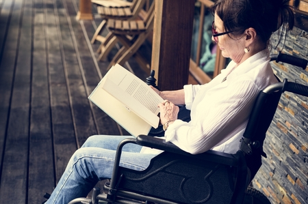 A woman sitting on a wheelchair and reading 版權商用圖片 - 100175789