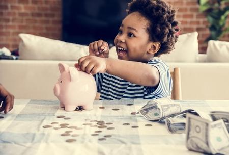 Black boy collecting money to piggy bank Imagens