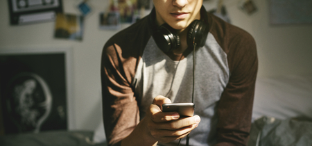 Teenage boy in a bedroom listening to music through his smartphone Imagens