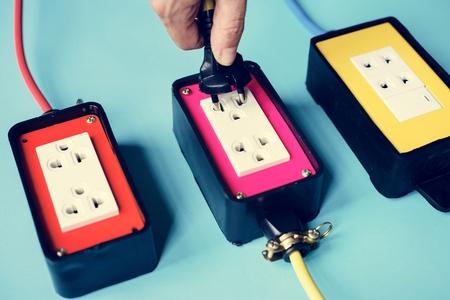 Electrical power supply plugs on blue background Standard-Bild - 100102102