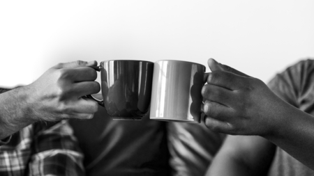 Men toasting coffee cup together