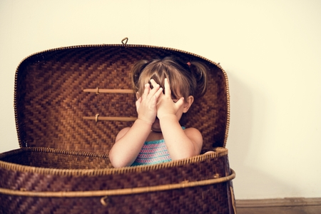 Little girl sitting in the basket and hands covering face Foto de archivo