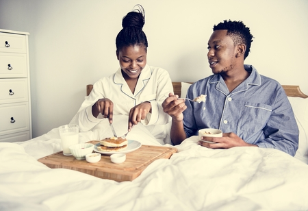 A couple having breakfast in bed Stock Photo