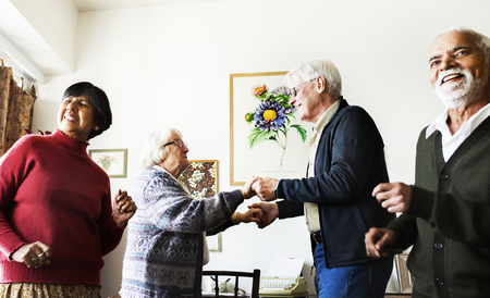 Senior friends dancing together at home