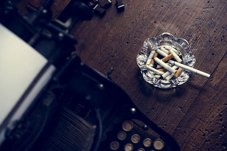Typewriter and tray of cigarette on wooden table Stock Photo