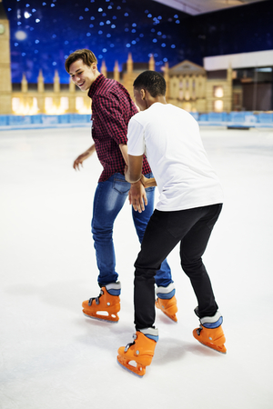 Friend teaching a friend how to ice skate friendship and leisure concept
