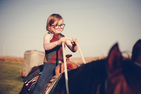 Young girl is enjoying a horse riding Reklamní fotografie