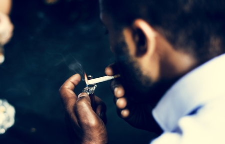 Rear view of man lighting up the cigarette in his mouth Stock fotó