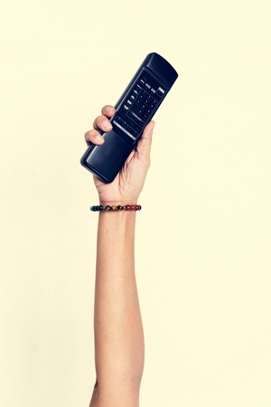 Hand holding remote control isolated on background 写真素材