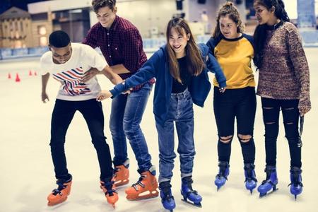 Gruppo di amici adolescenti pattinaggio su ghiaccio su una pista di pattinaggio