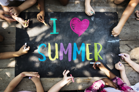 Group of kids writing summer on a chalkboard