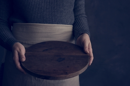 Woman in an apron holding a wooden tray Reklamní fotografie