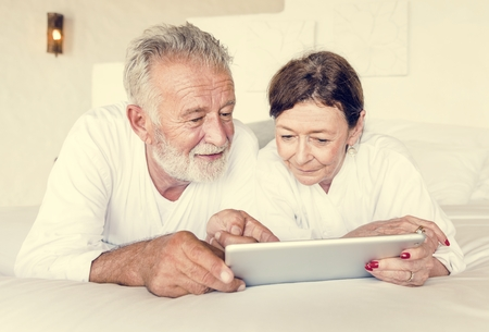 Senior couple using a tablet in bed Stock Photo
