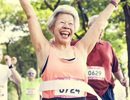 Elderly asian woman reaching the finish line Stock Photo