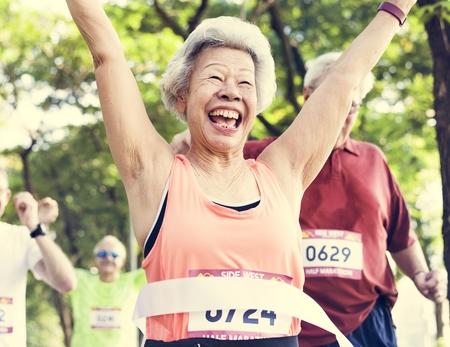 Femme asiatique âgée atteignant la ligne d'arrivée