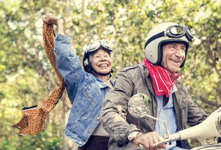 Senior couple riding a classic scooter Stock Photo