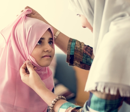 Muslim mother putting on a hijab on her little daughter Stock Photo