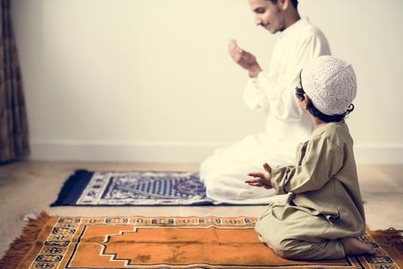 Muslim boy learning how to make Dua to Allah Foto de archivo
