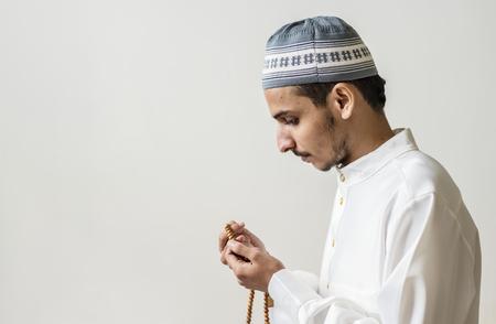 Muslim man praying with tasbih during Ramadan