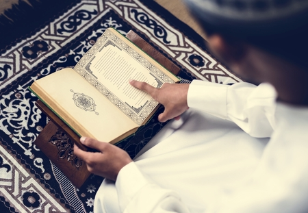 Muslim man studying The Quran Stock Photo