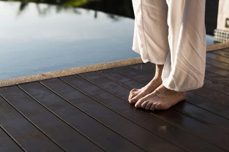 Senior adult practicing yoga by the pool 版權商用圖片