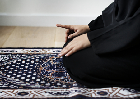Muslim woman praying in Tashahhud posture
