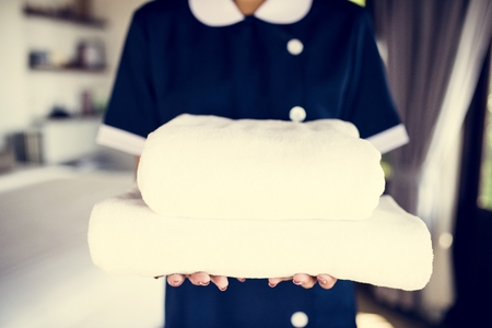 Housekeeper handing a new set of towels Stock Photo