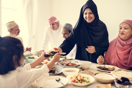 Muslim woman sharing food at Ramadan feast