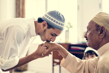 Young Muslim man showing respect to his father Standard-Bild - 102863013