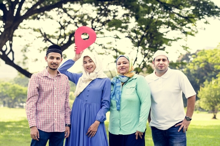 Muslim family holding up a check point symbol