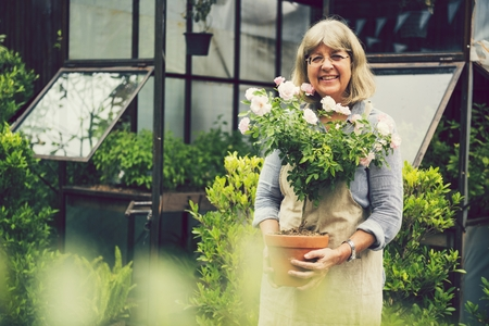 Mature woman tending to her plants Stock Photo