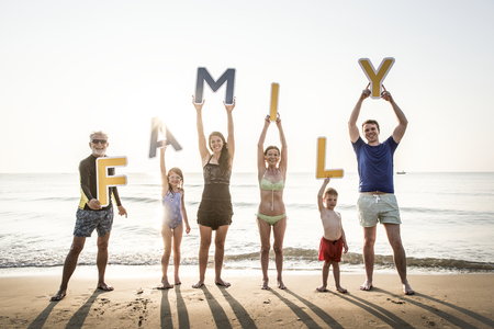 Family holding up letters at the beach