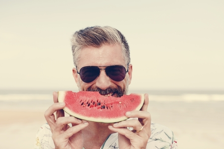 Mature man eating watermelon at the beach