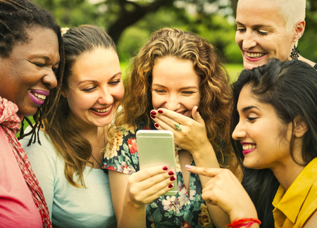 Friends laughing at something on a phone Stock Photo