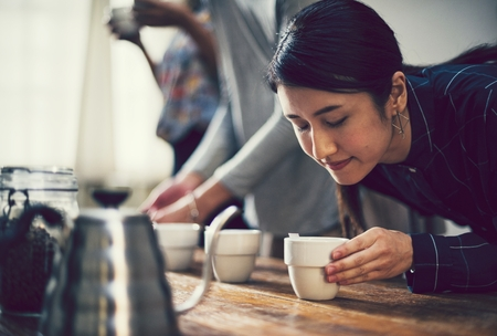 Woman smelling the aroma of a cup of coffee Standard-Bild