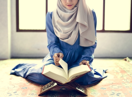 Muslim woman reading from the quran Stock Photo - 102861342
