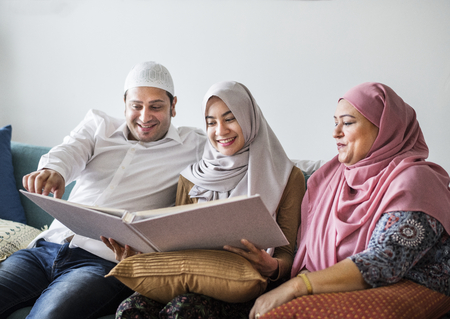Muslim family looking in a photo album Stock Photo - 102863374