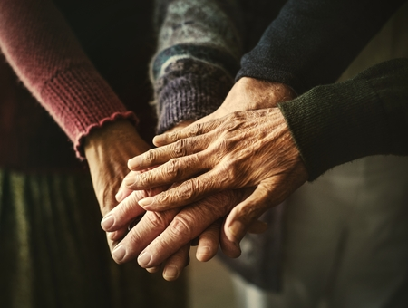 Elderly group of friends stacking hands