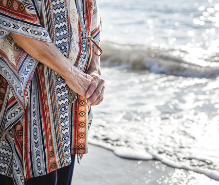 Mature woman standing at the beach Stock Photo