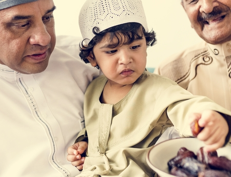 Muslim boy eating dried dates Stock Photo