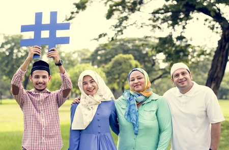 Muslim family holding up a hashtag Stock Photo