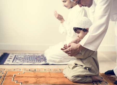 Moslimjongen die leert hoe hij Dua bij Allah moet maken Stockfoto