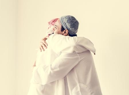 Muslim men hugging each other Stock Photo