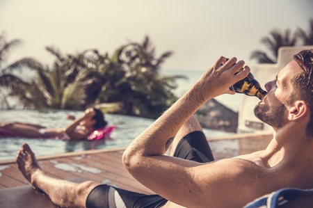 Bearded man drinking beer by the pool
