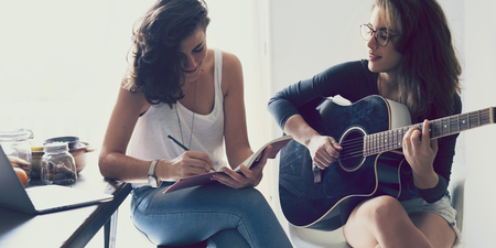 Lesbian couple playing guitar in their home